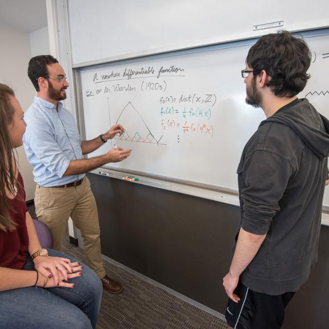 professor teaching two students on a whiteboard